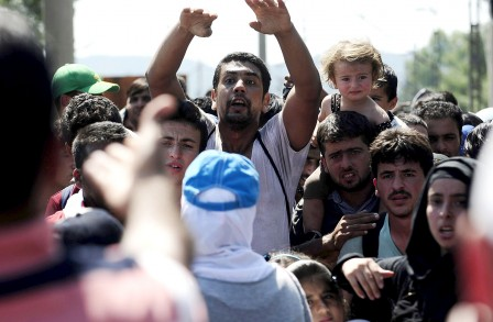 Migrants standing at the Greek side of the border wait to cross into Macedonia, near Gevgelija